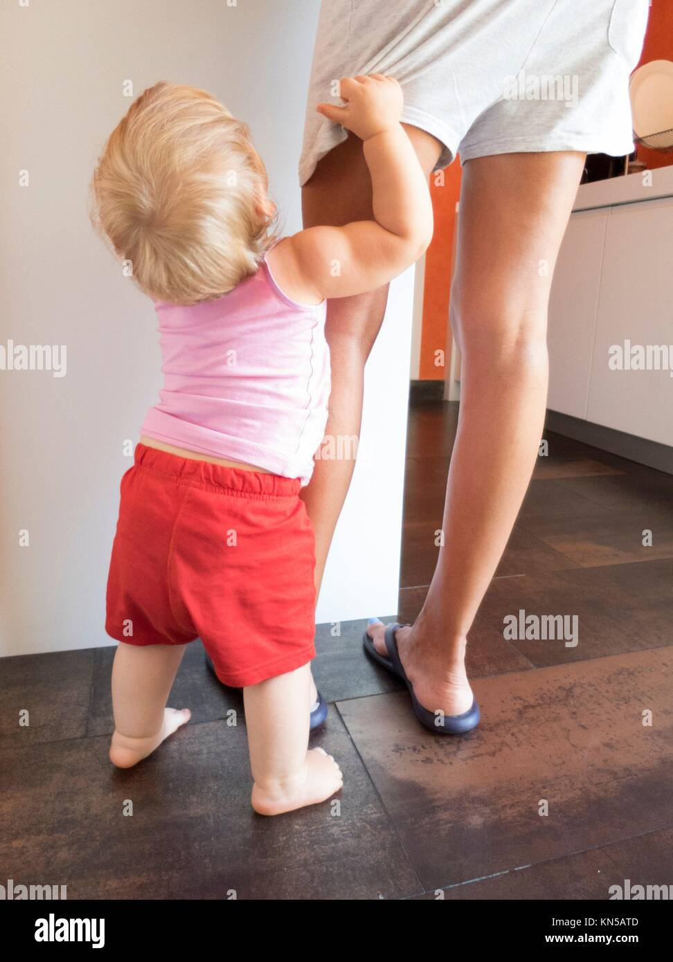 blonde baby red shorts clutching mom leg in white kitchen. - Stock Image