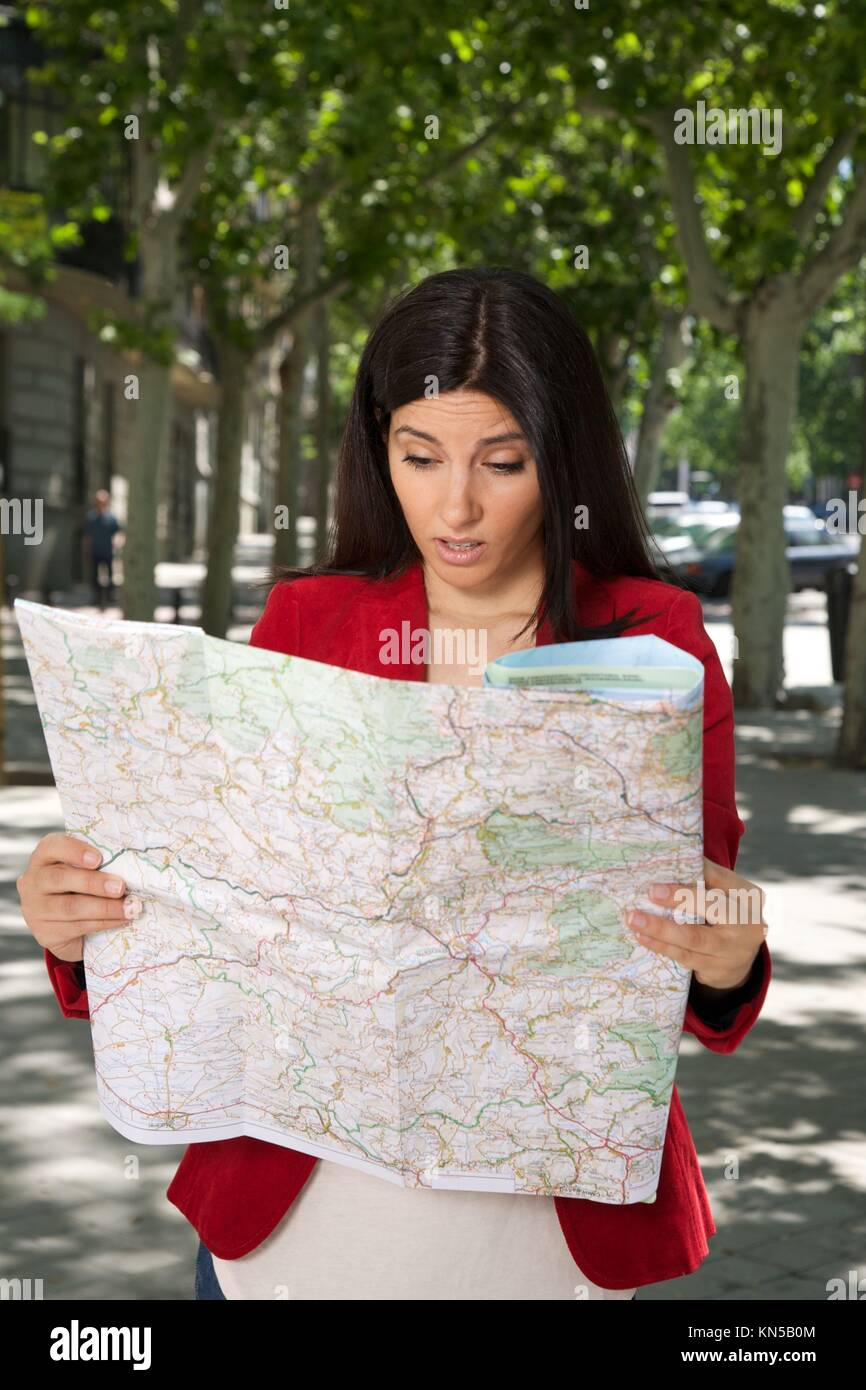 angry brunette woman watching a map at street in Madrid city Spain. - Stock Image