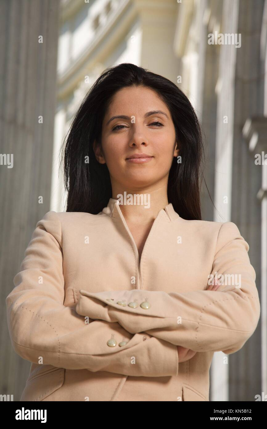 businesswoman in challenging pose between columns looking at you. - Stock Image