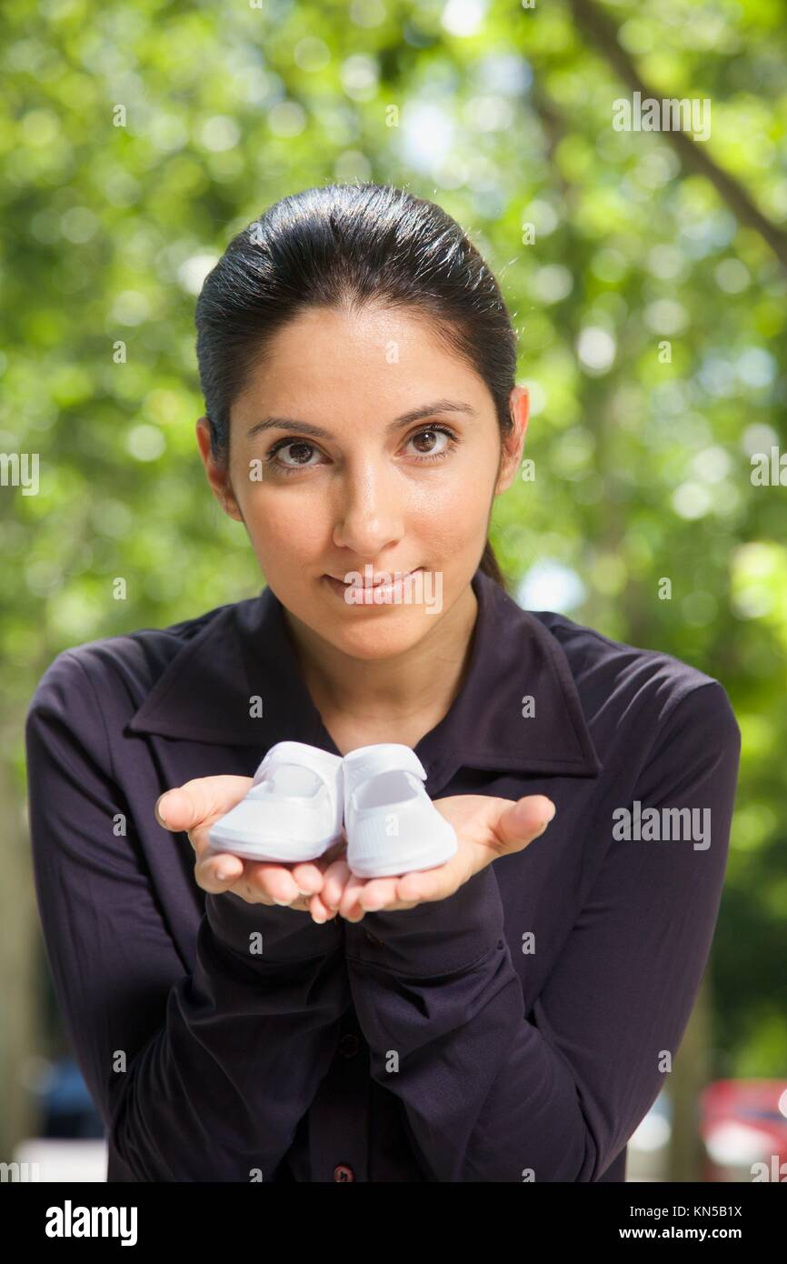 woman with booties on her hand on green natural background. - Stock Image