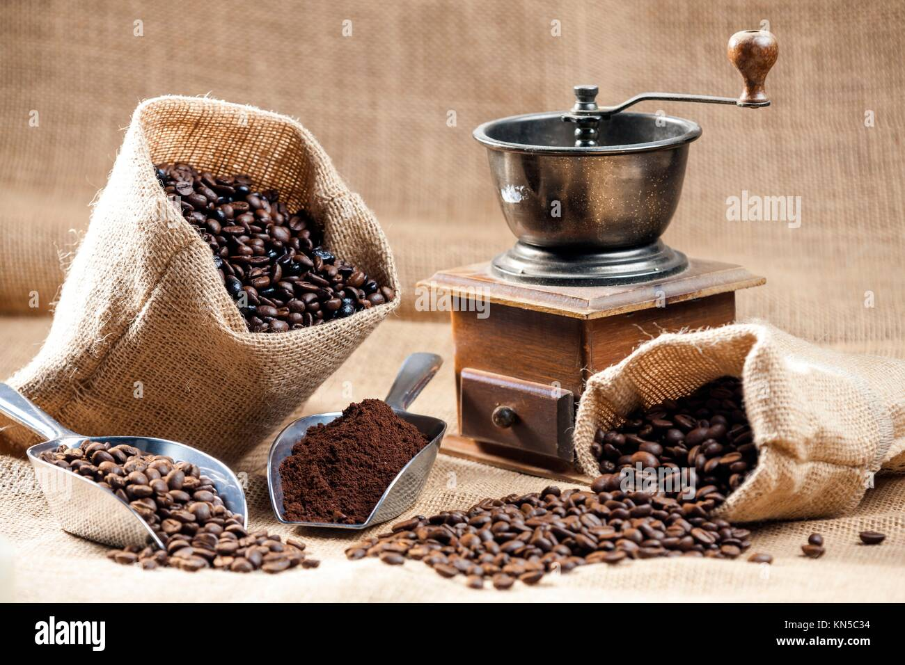 still life of coffee beans in jute bags with coffee grinder. Stock Photo