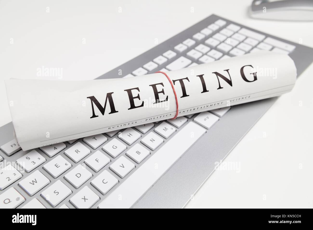 meeting written on newspaper on keyboard. - Stock Image