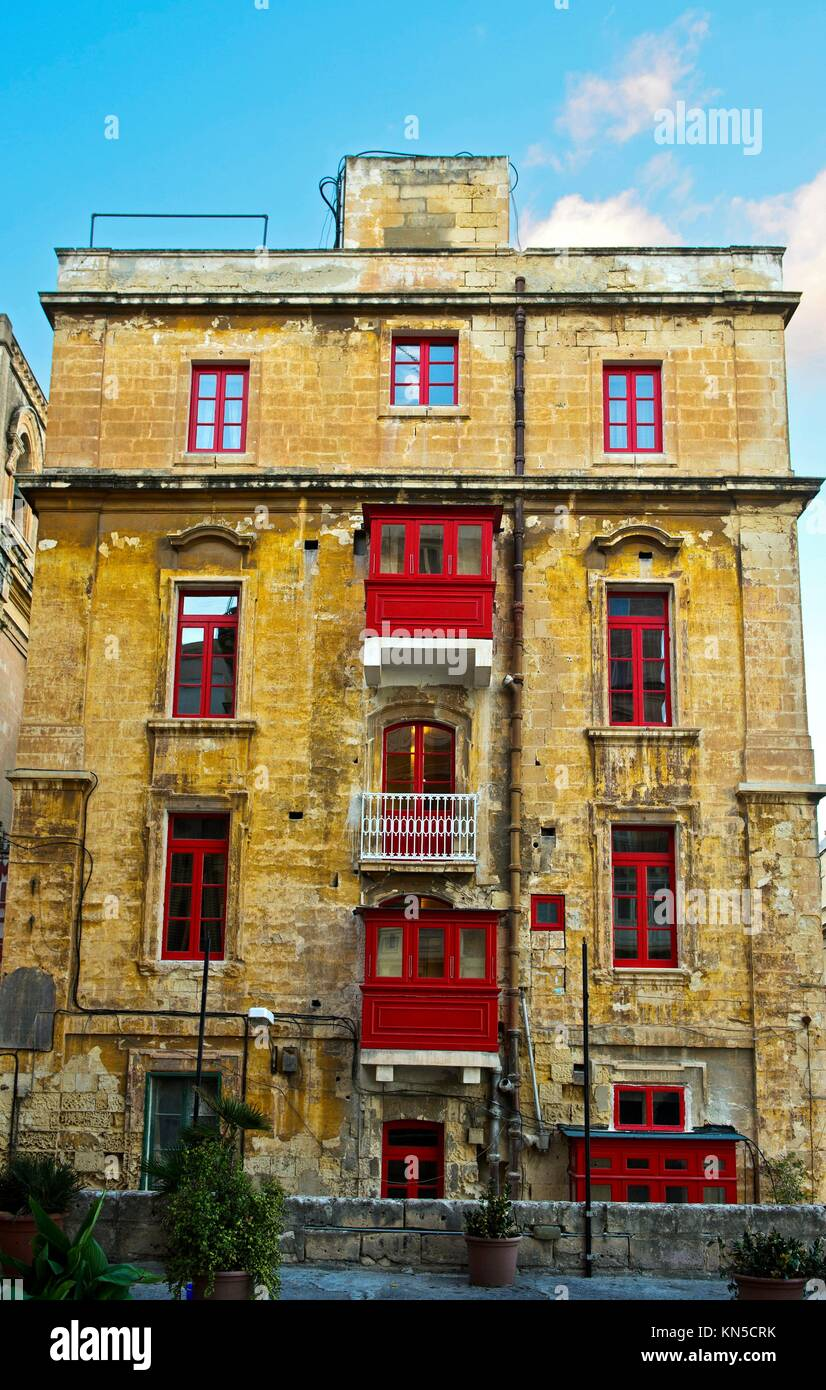 Decrepit house with new red windows, Valletta, European Capital of Culture 2018, Malta. - Stock Image