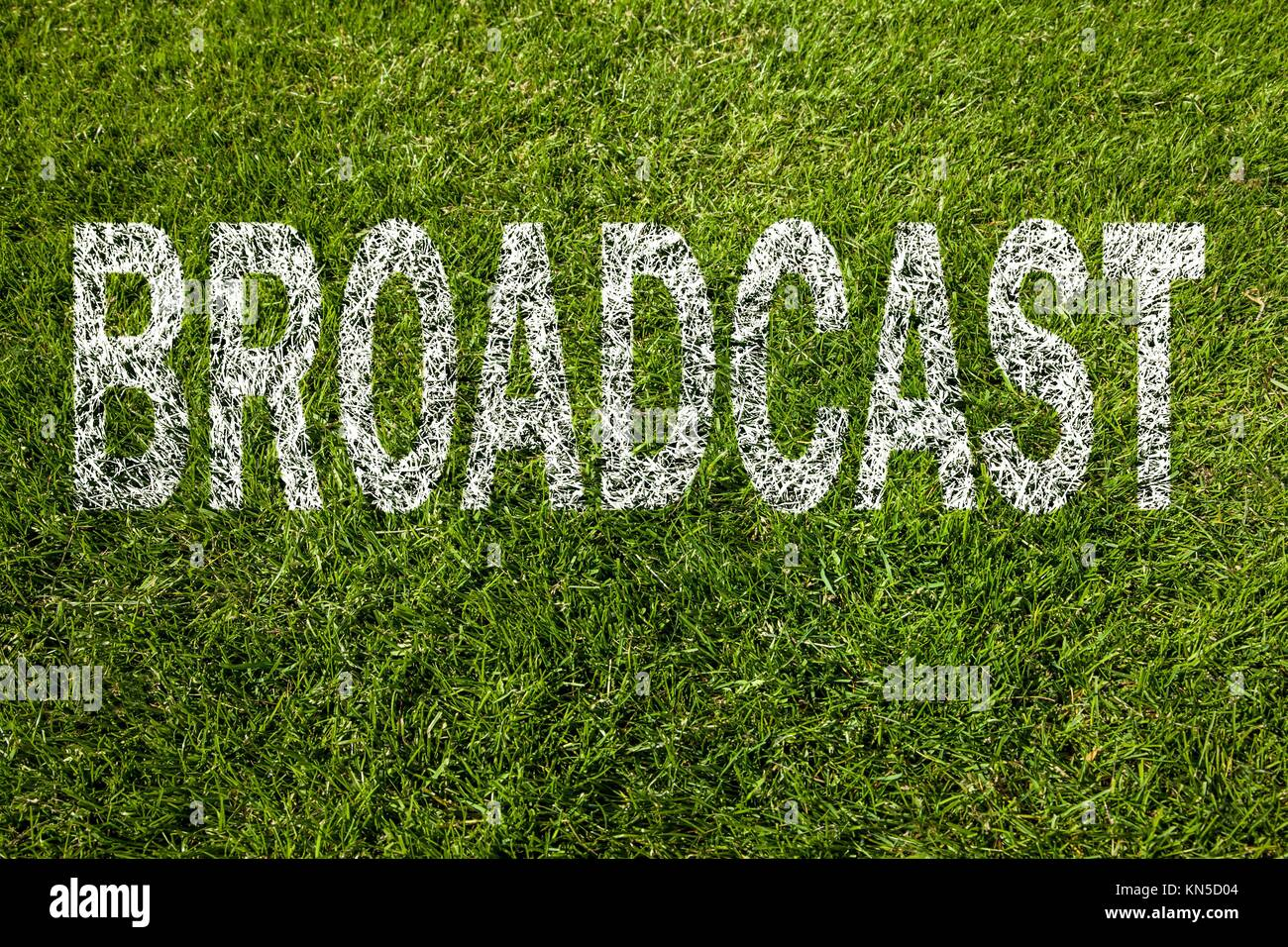 broadcast written on a green meadow. - Stock Image