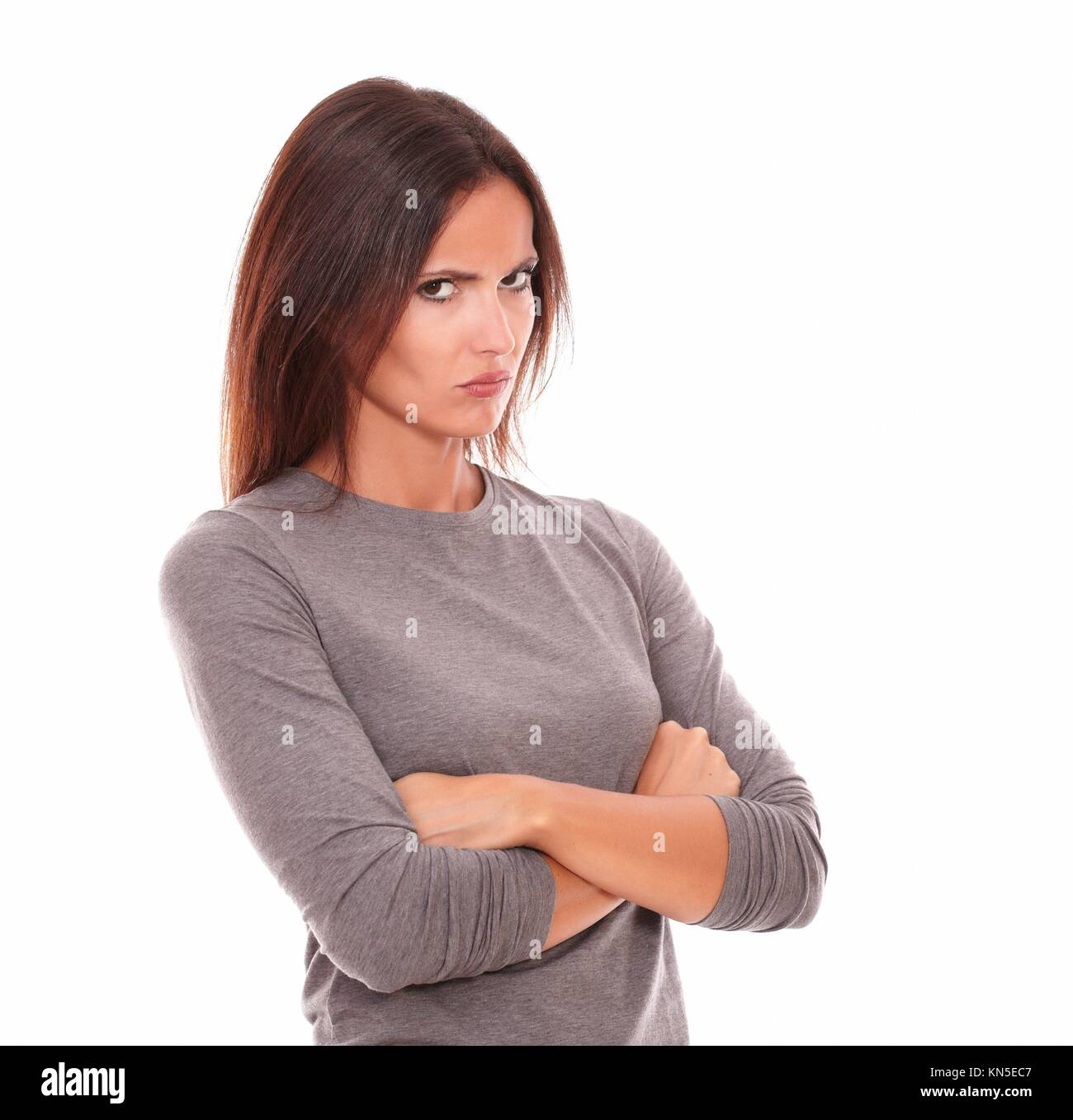 Unhappy brunette in grey blouse looking angry and serious in white background. - Stock Image