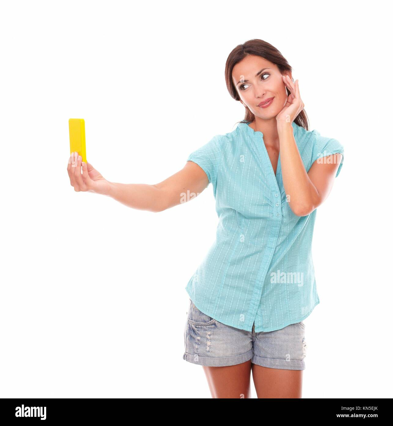 Attractive female taking photos of herself or selfie using a yellow mobile phone while smiling in white background. - Stock Image
