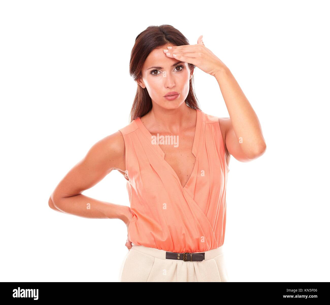 Lovely lady suffering from migraine headache with hand on head and looking at you in white background. - Stock Image