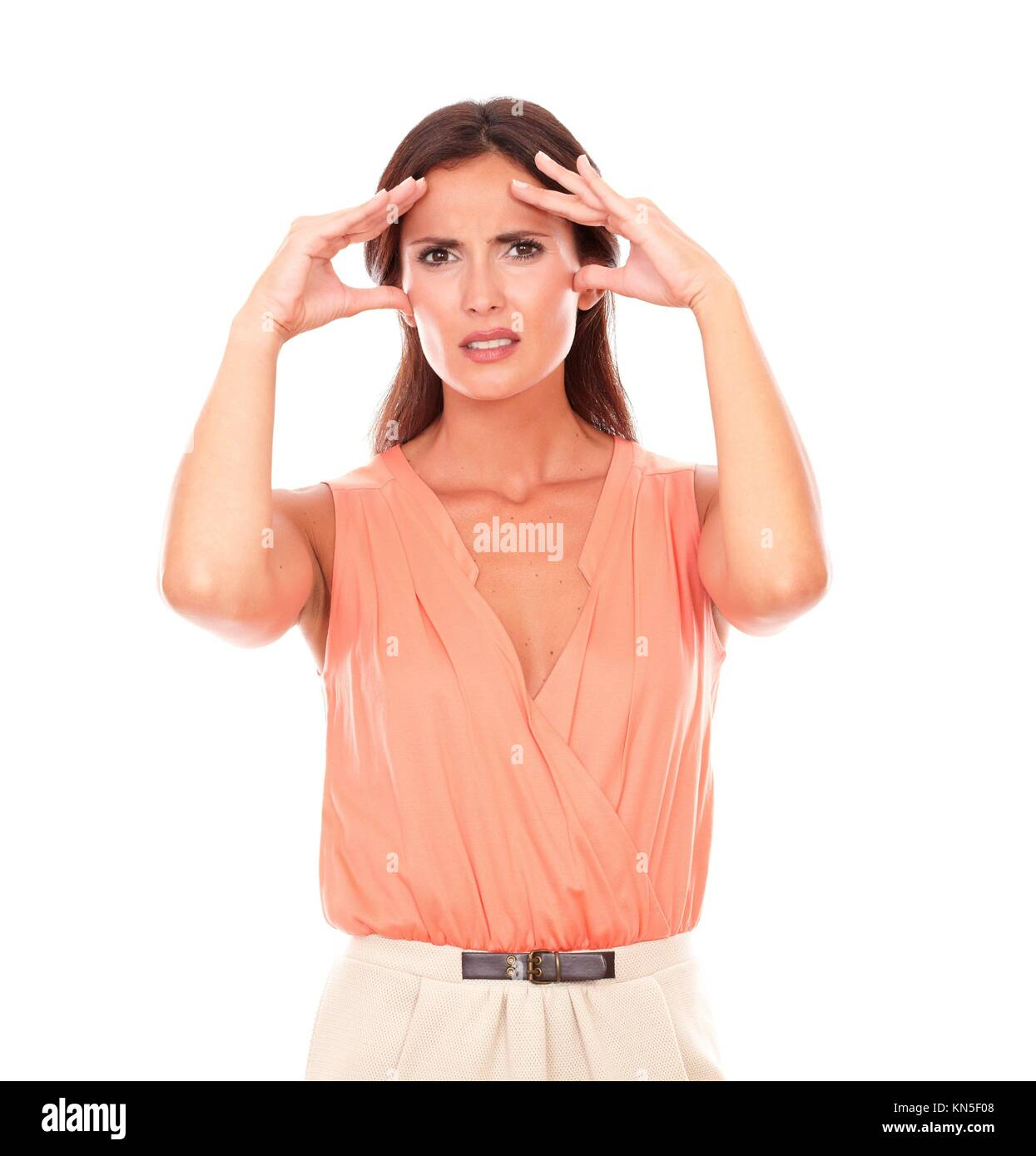 Hispanic female suffering from migraine headache with hand on head and looking at you in white background. - Stock Image