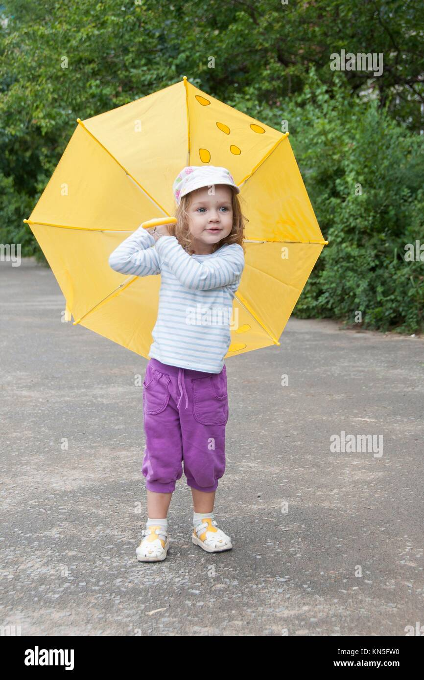 Merry little girl stands with the yellow umbrella on an asphalt road on the street. - Stock Image