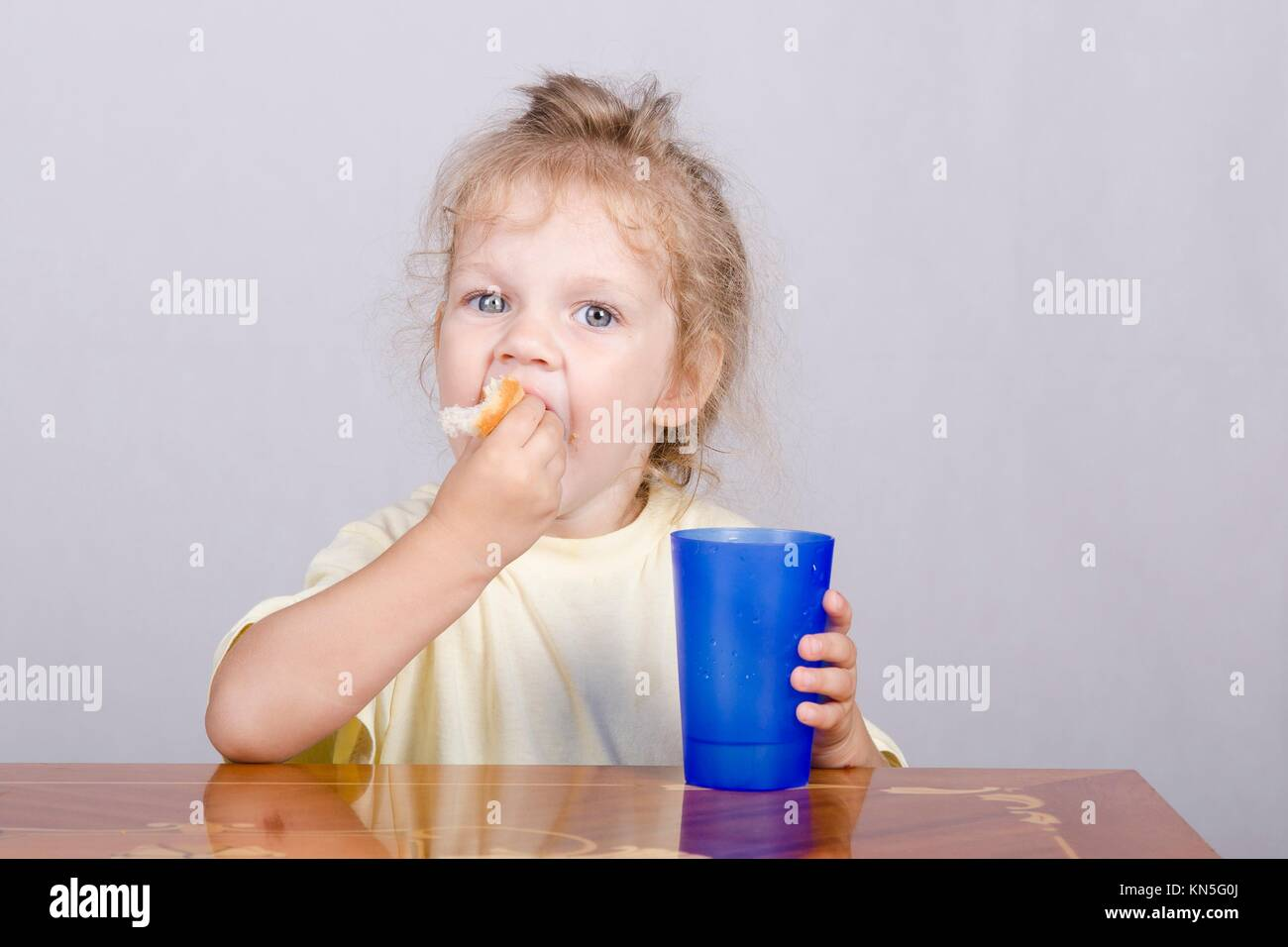 Two-year-old girl sitting at the table, eating a muffin and drinking from a plastic Cup. Stock Photo