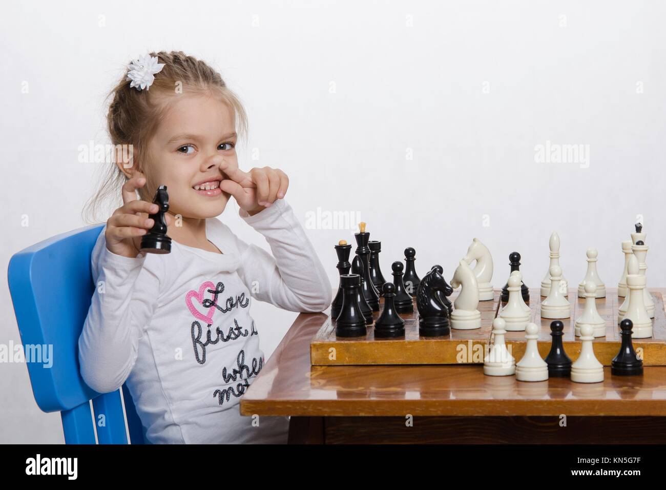 Four-year-old girl playing in chess. A girl holding a hand shape, finger of the other hand tucked into the nose. - Stock Image