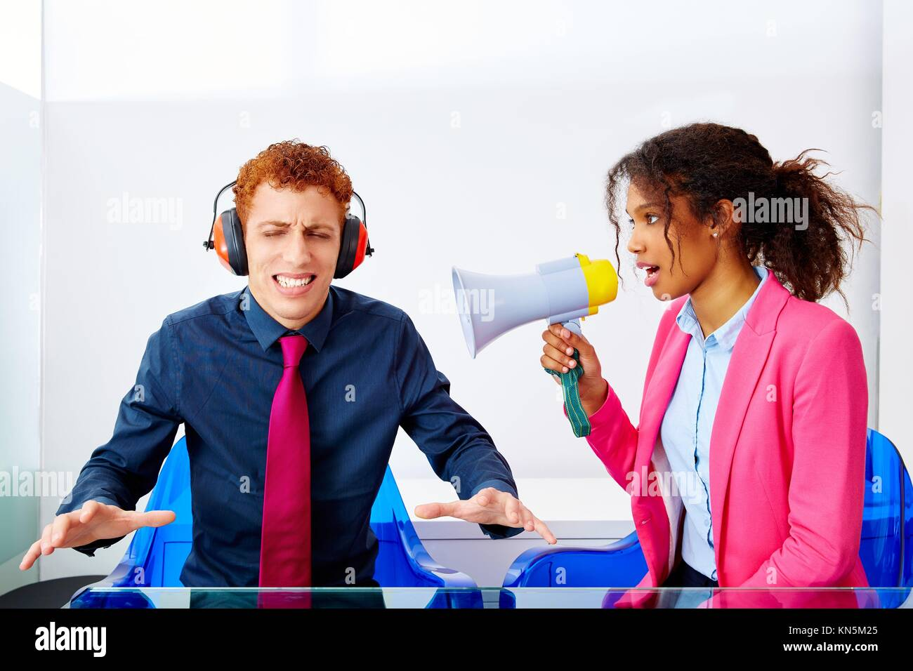 business woman talking in megaphone african ethnicity to young executive. - Stock Image