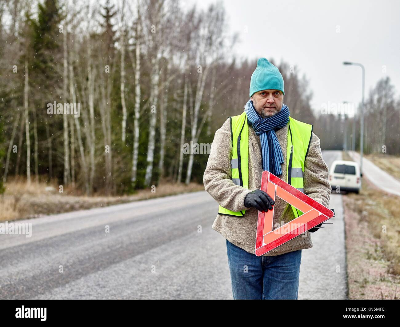 Mid adult man wearing reflector vest and he have a red warning triangle - road and vehicle on background. - Stock Image