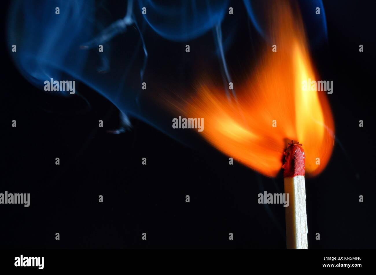Burning match over black background. - Stock Image