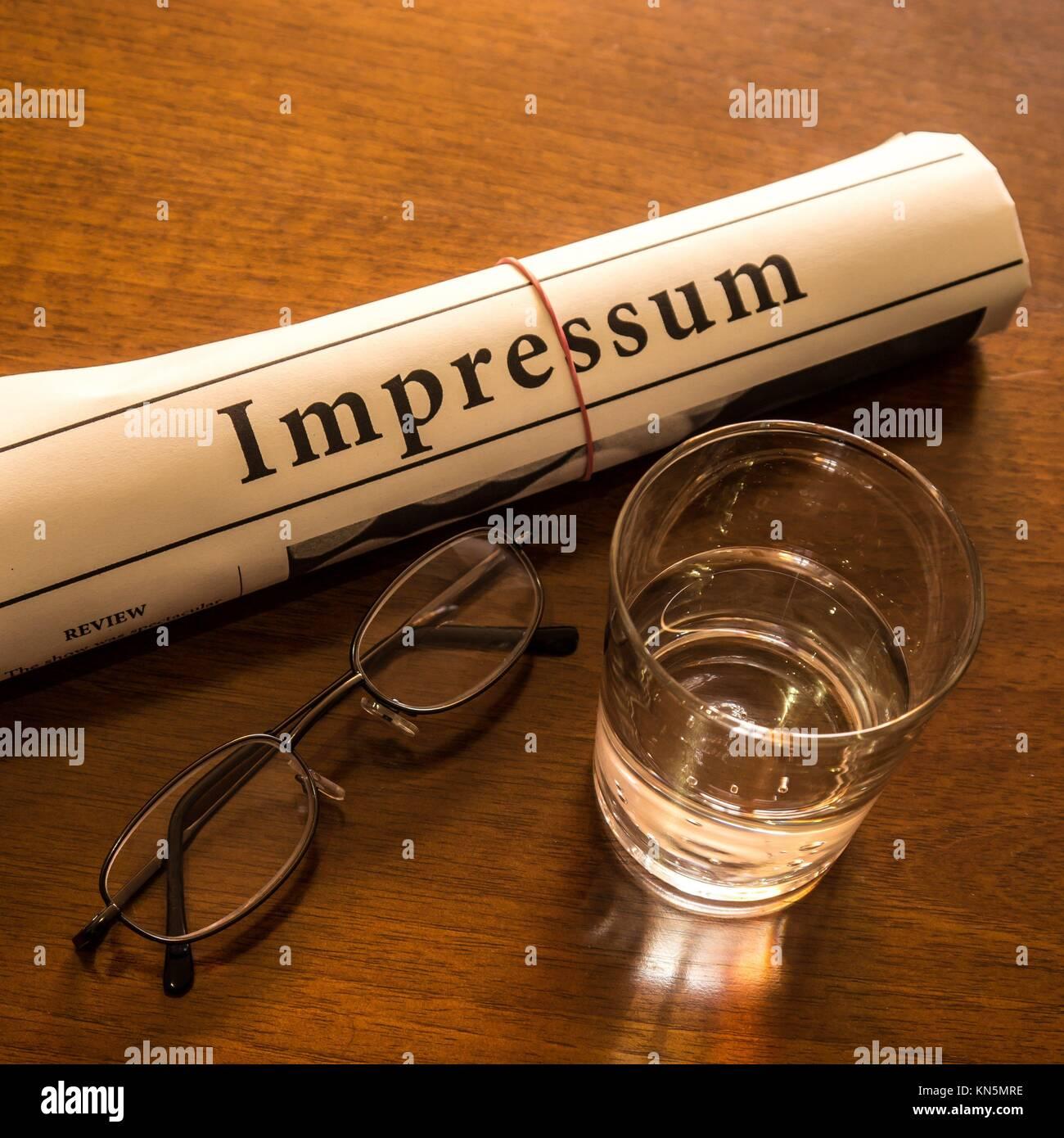 impressum, glass water, glasses on desk. - Stock Image