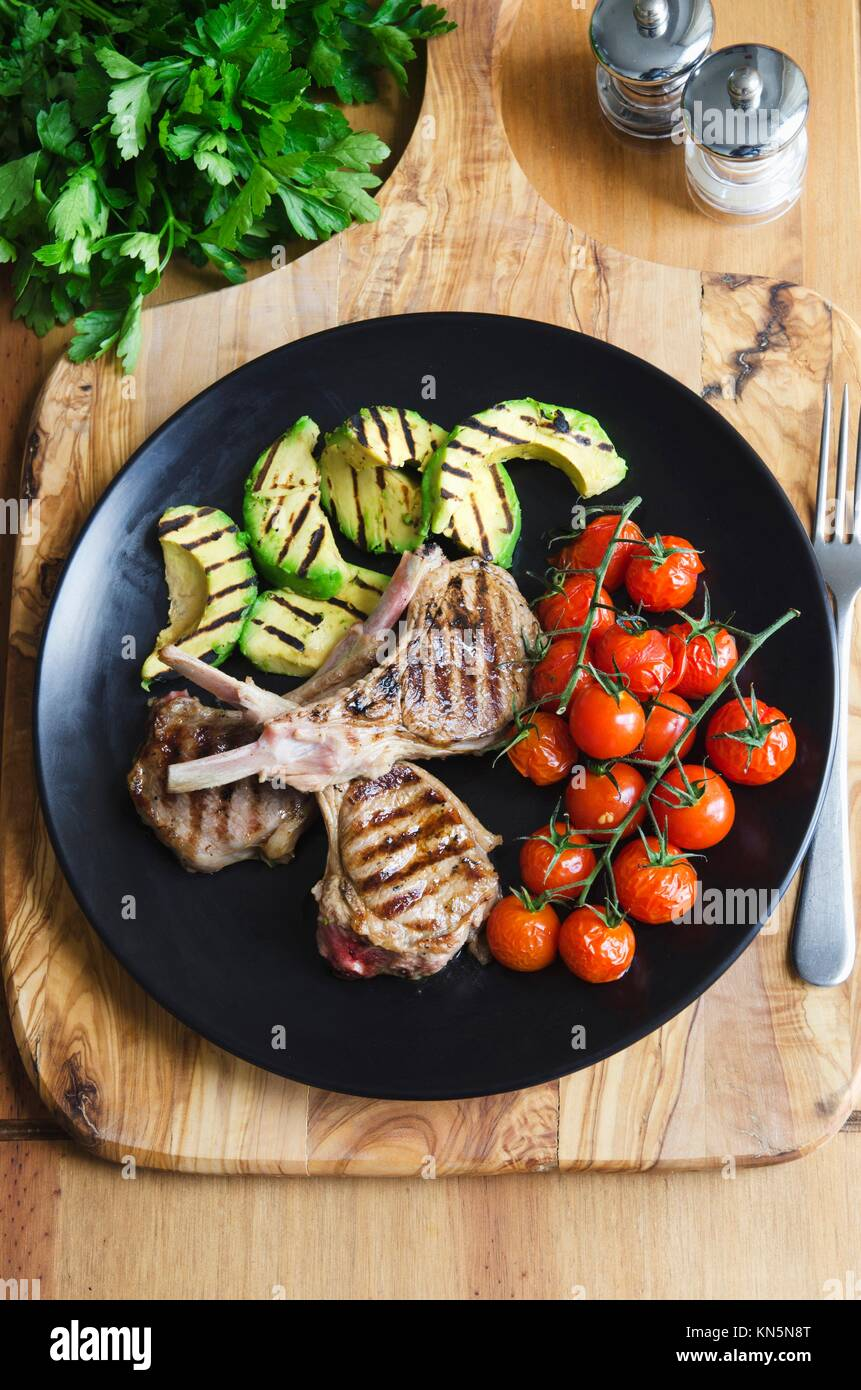Griddled lamb cutlets with avocado and cherry tomatoes. - Stock Image