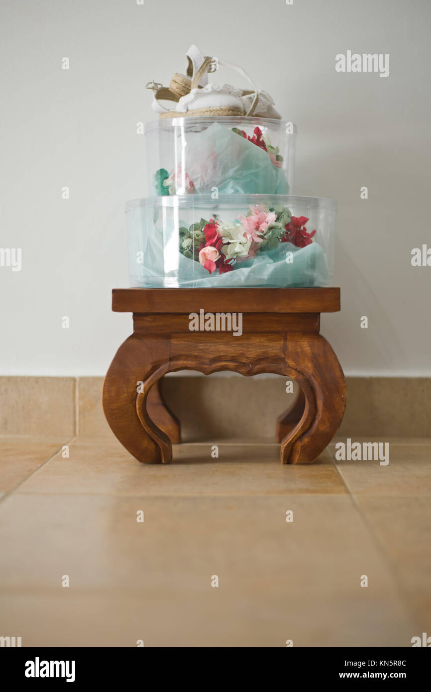 Floral white bridal headdress and shoes on their boxes over wooden footstool. - Stock Image
