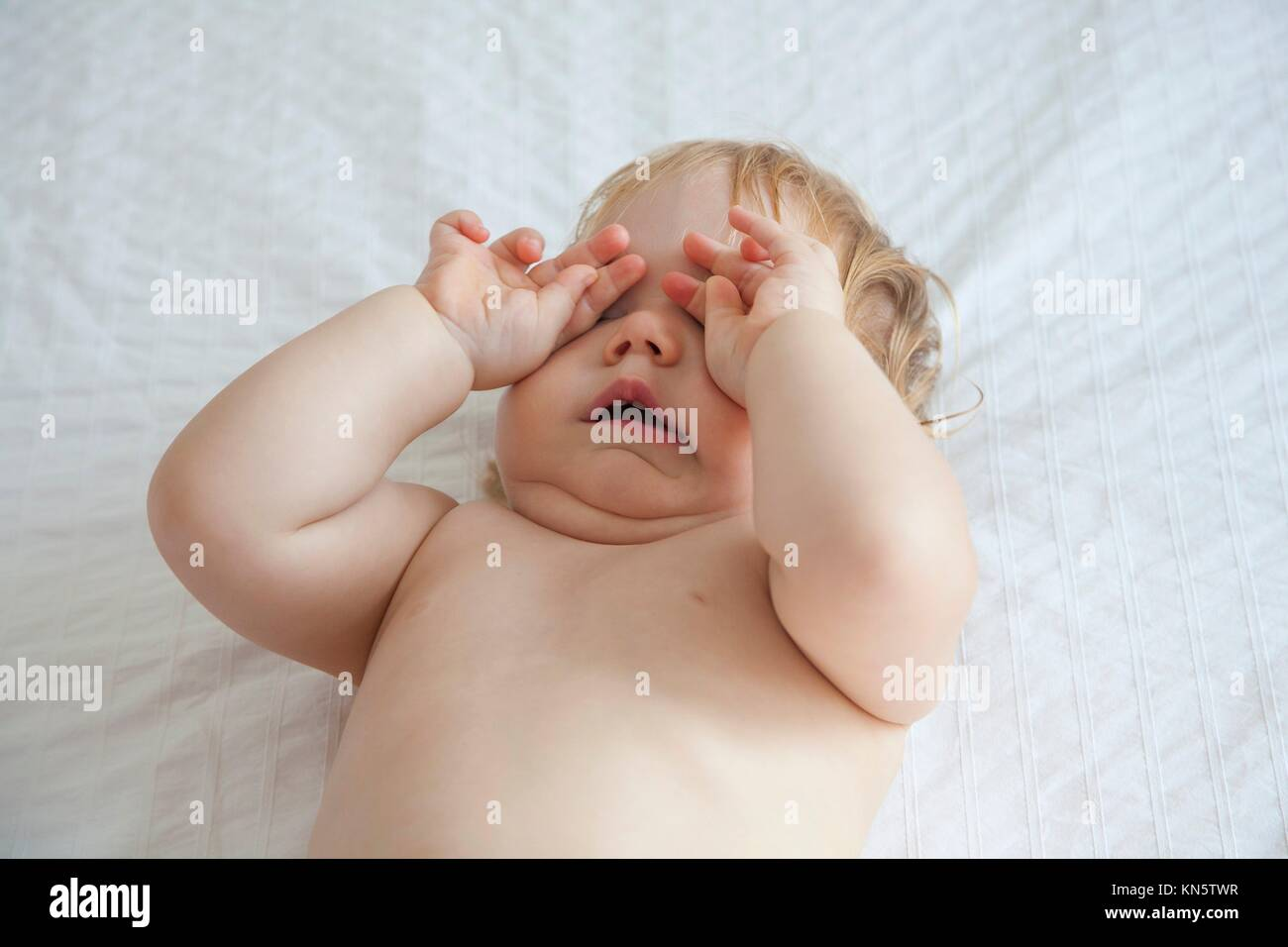 one year blonde baby diaper yawning and touching her eyes over white bedcover. - Stock Image