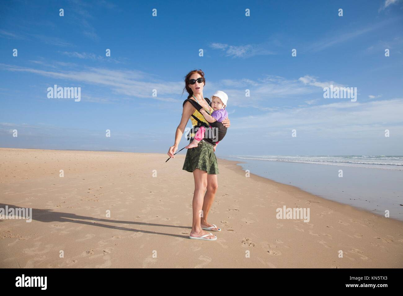 mother with green miniskirt black sunglasses carrying her one year baby with white hat in front rucksack walking - Stock Image