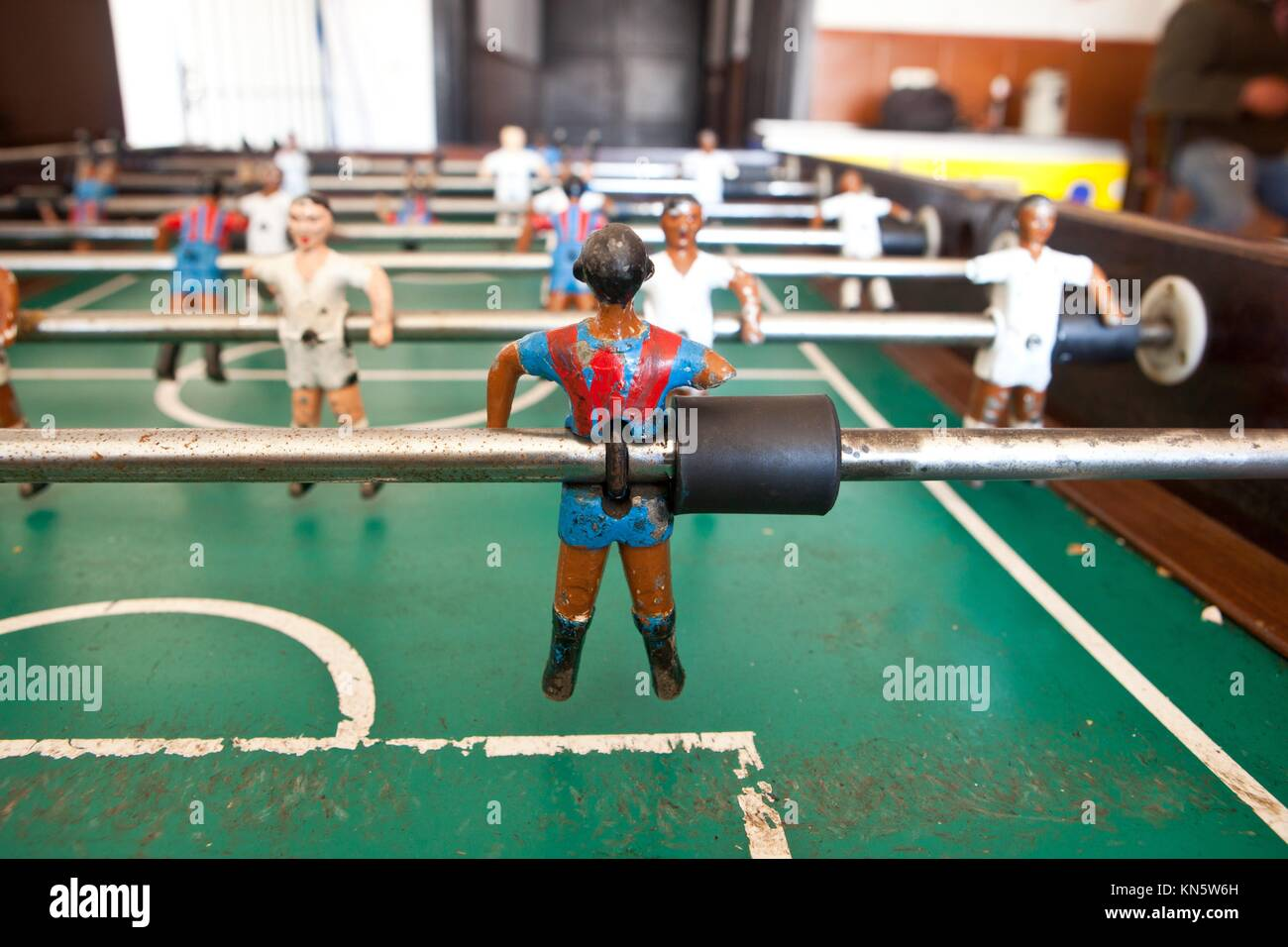 Table football in the bar, visible figures of toy mini football players wearing Real Madrid and Barcelona soccer - Stock Image