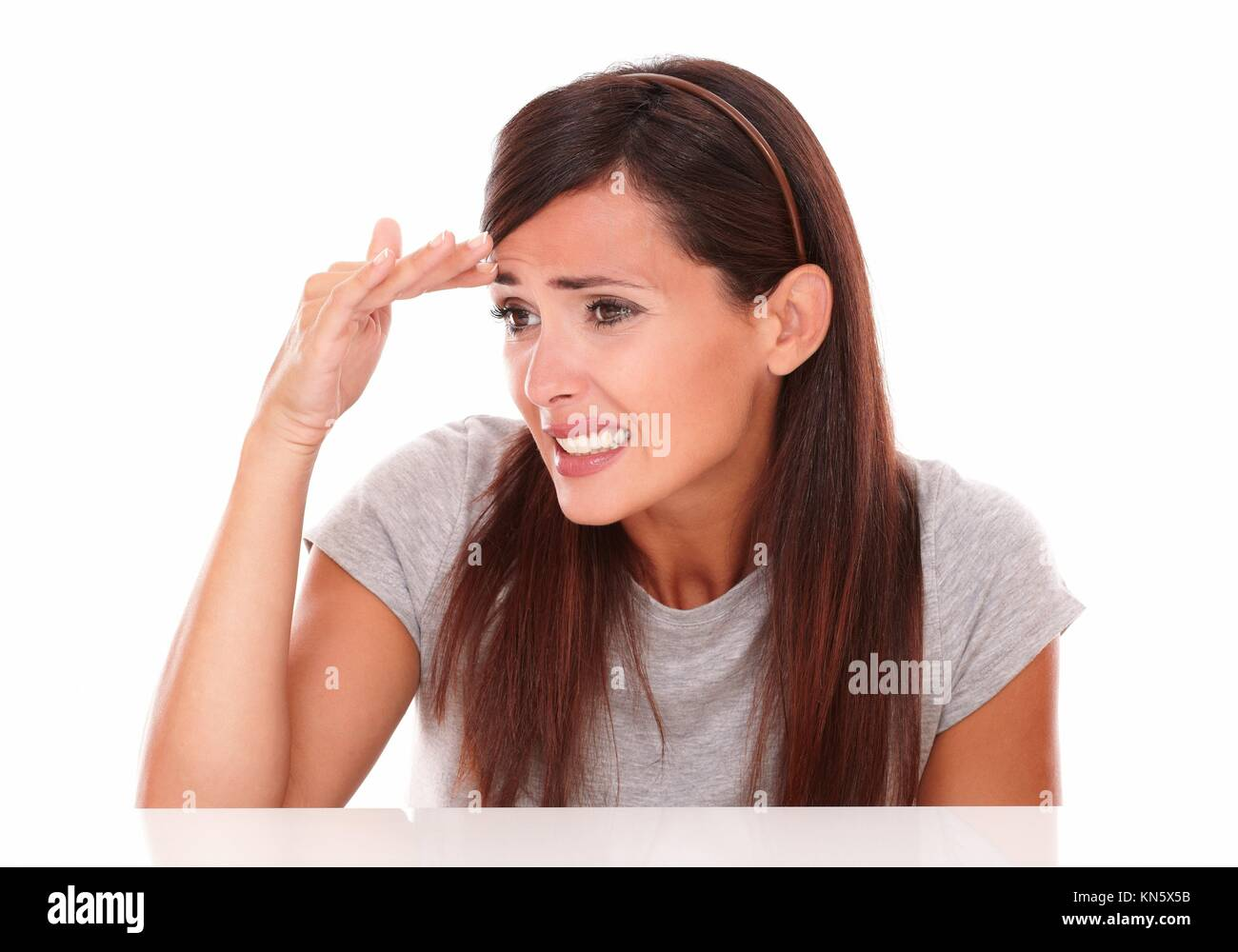 Headshot portrait of cute young woman with fail gesture looking to her right on isolated studio. - Stock Image