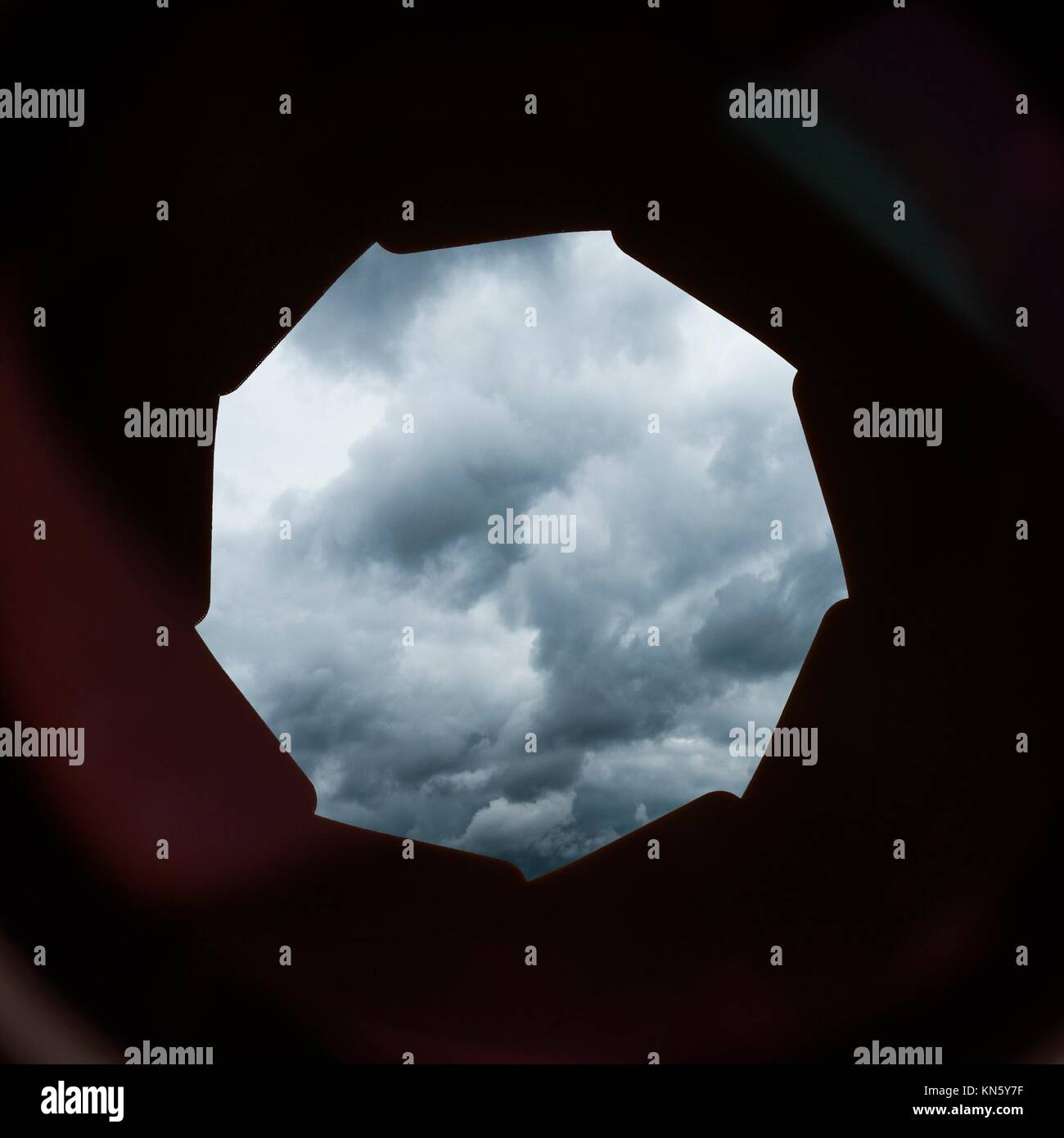 Sky with storm clouds seen through the lens and aperture of a camera. Moody and conceptual image of trouble, difficulty - Stock Image