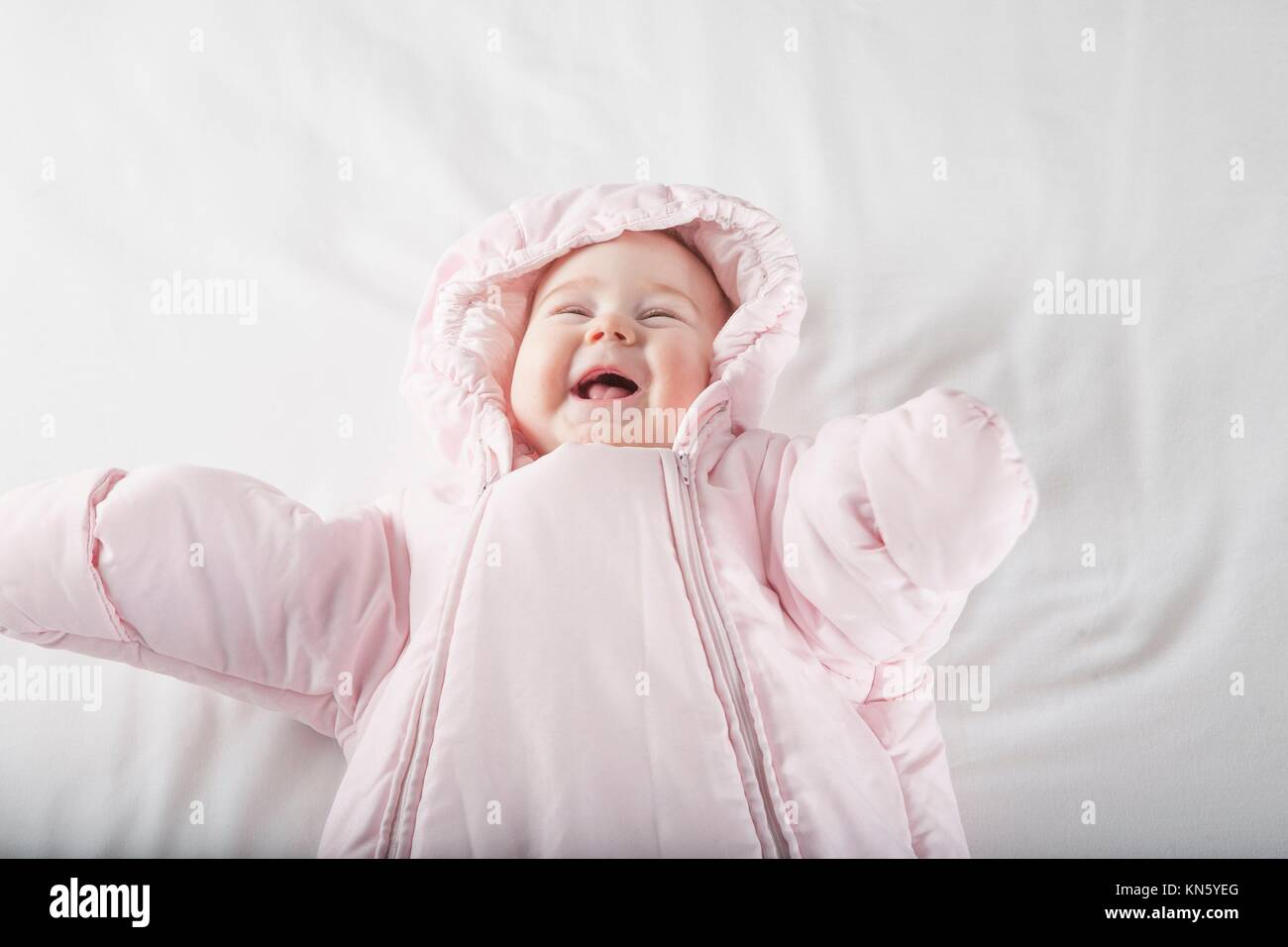 six months age cute baby dressed up in pink fluffy winter snowsuit snug hoodie clothes lying on white sheet bed - Stock Image