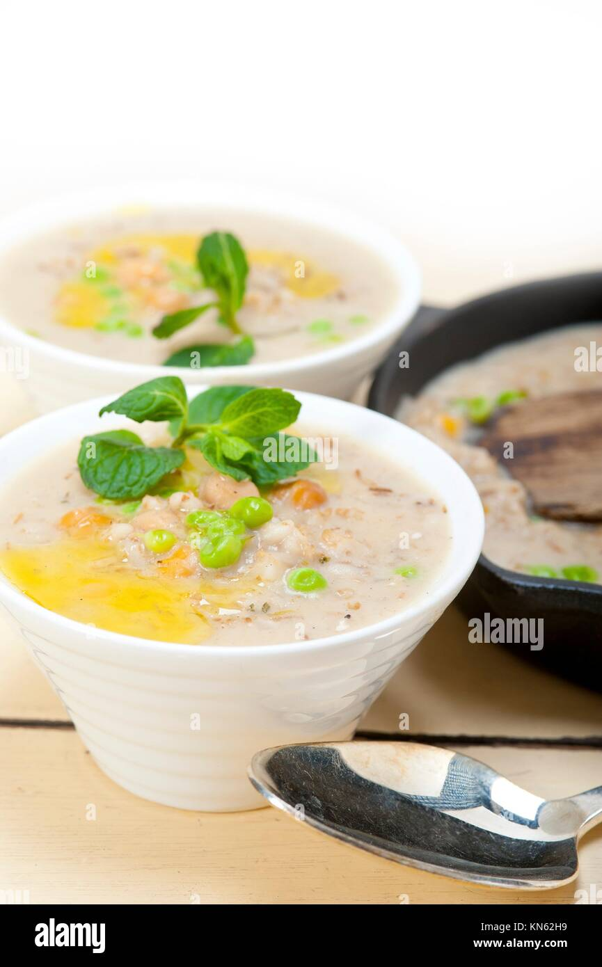 Hearty Middle Eastern Chickpea and Barley Soup with mint leaves on top. - Stock Image