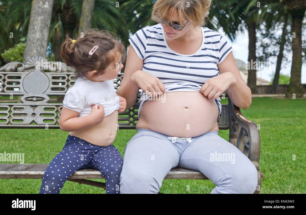 Toddler girl playing with her mother tummy. They are showing their belly. - Stock Image