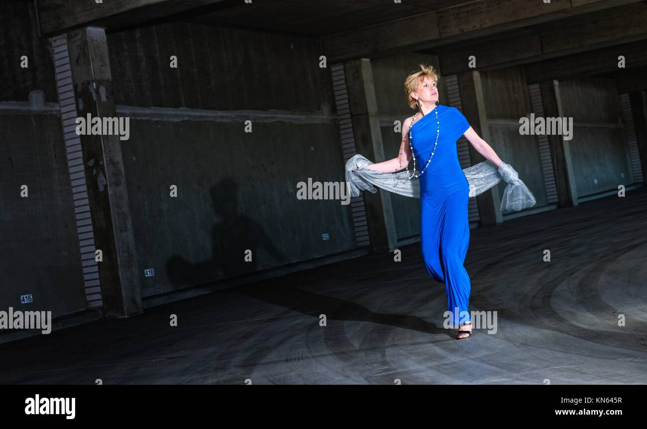 Frightened woman wearing blue dress and running in the public parking house. - Stock Image