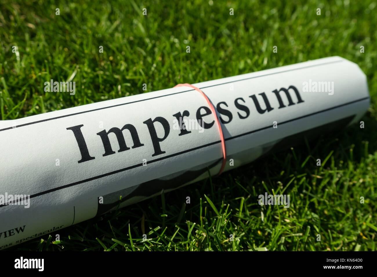 impressum newspaper on green meadow. - Stock Image