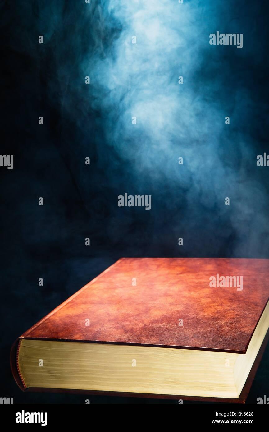 Floating unopened book and smoke, dark background, close up. - Stock Image