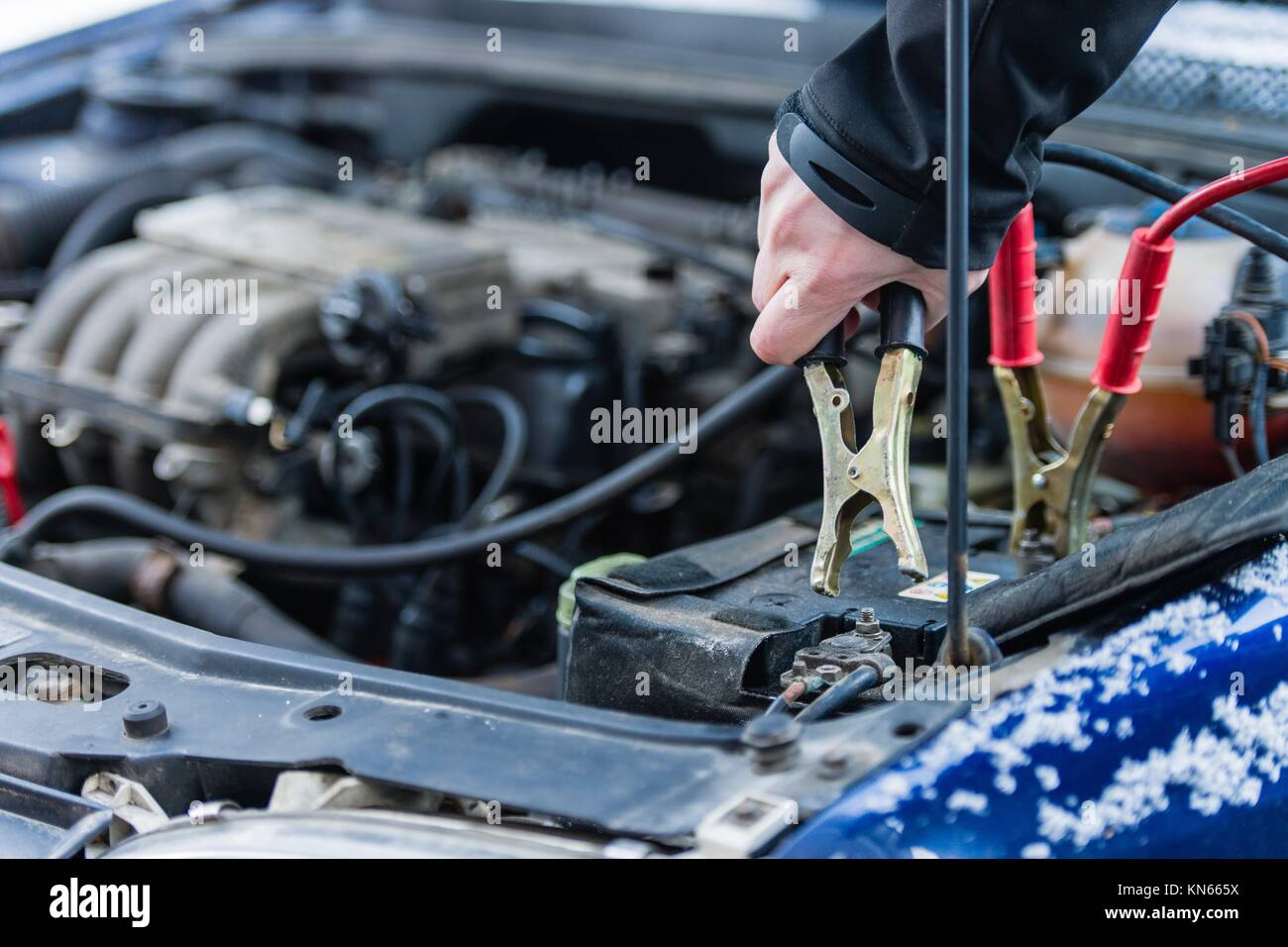 The booster cables and discharged battery, cold winter day. - Stock Image