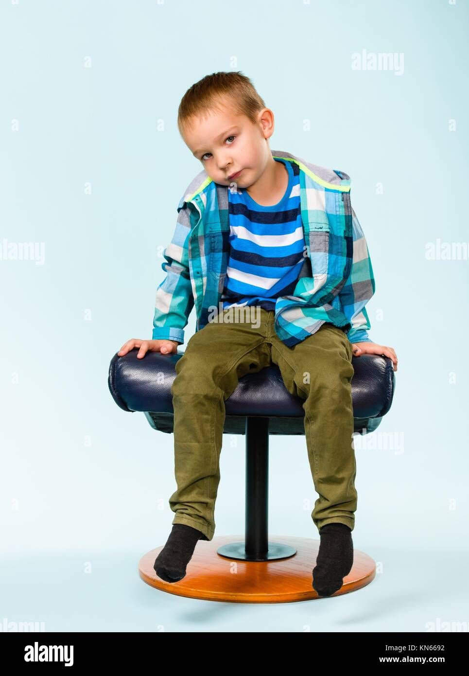 Little boy on posing with a footstool, studio shot and light blue background. - Stock Image