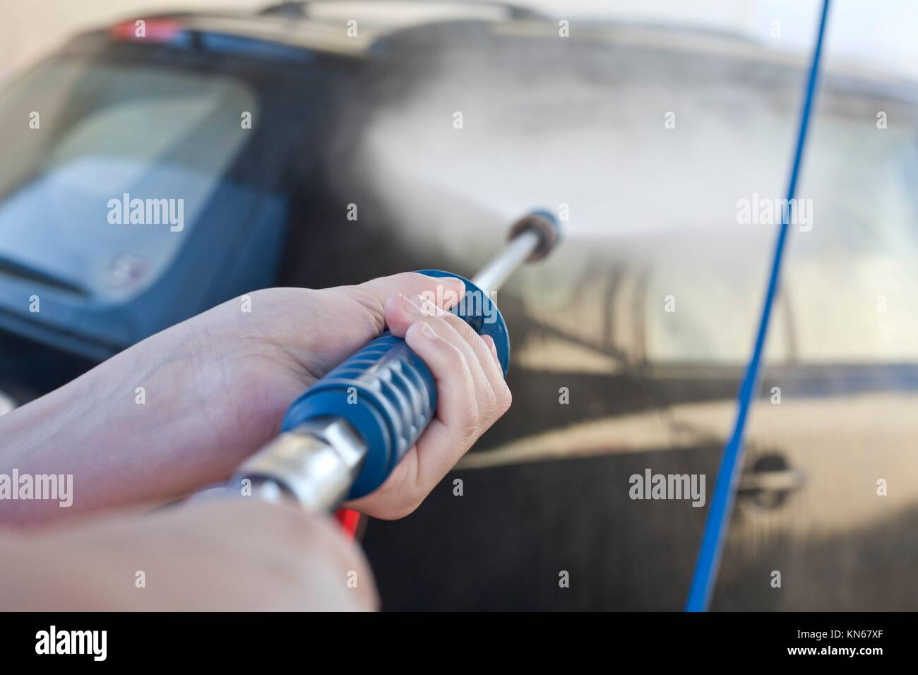 Washing with pressure gun my new black car. - Stock Image