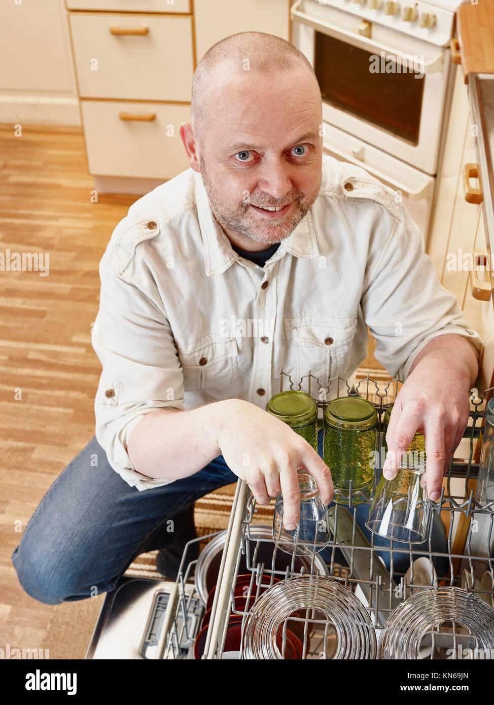 Homeworks, smiling man to fill the dishwasher. - Stock Image