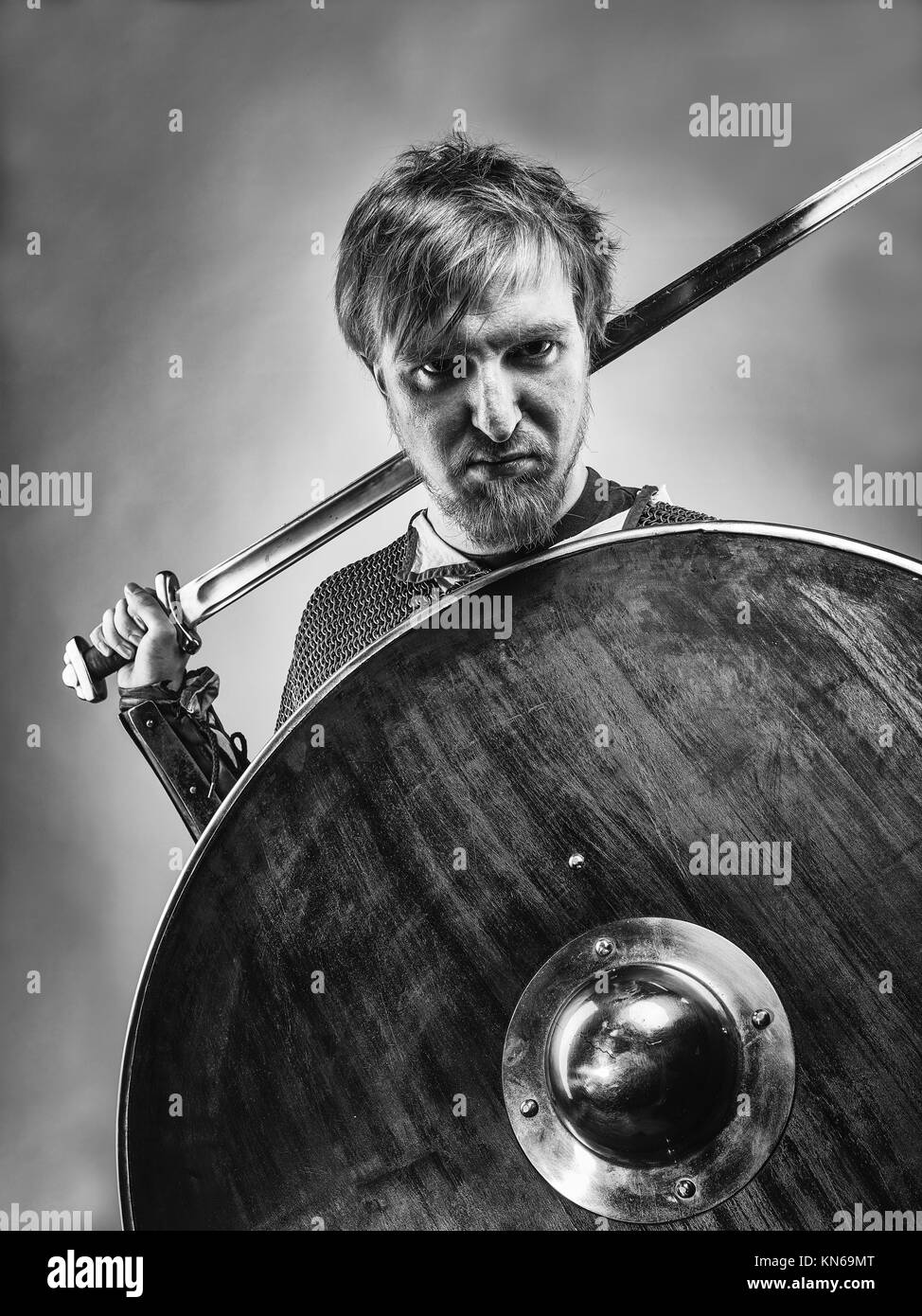 Angry medieval knight armor with a sword and shield, black and white image. - Stock Image