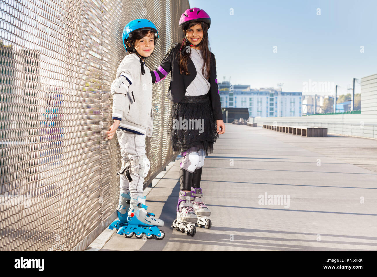 Portrait of preteen boy and girl in roller helmets rollerblading at sunny summer day - Stock Image