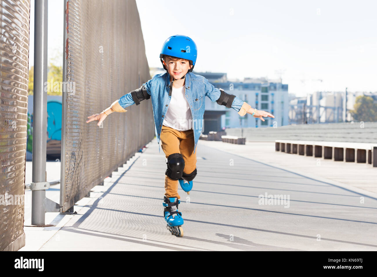 Portrait of preteen boy in helmet practicing rollerskating with his hands like wings at outdoor rollerdrome - Stock Image