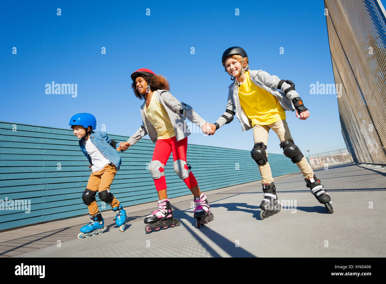 Happy preteen boys and girl in helmets holding hands while rollerblading outdoors - Stock Image