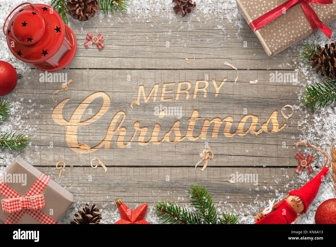 Creative hand carved Merry Christmas text in a wooden surface. Surrounded with Christmas decorations. Top view of - Stock Image