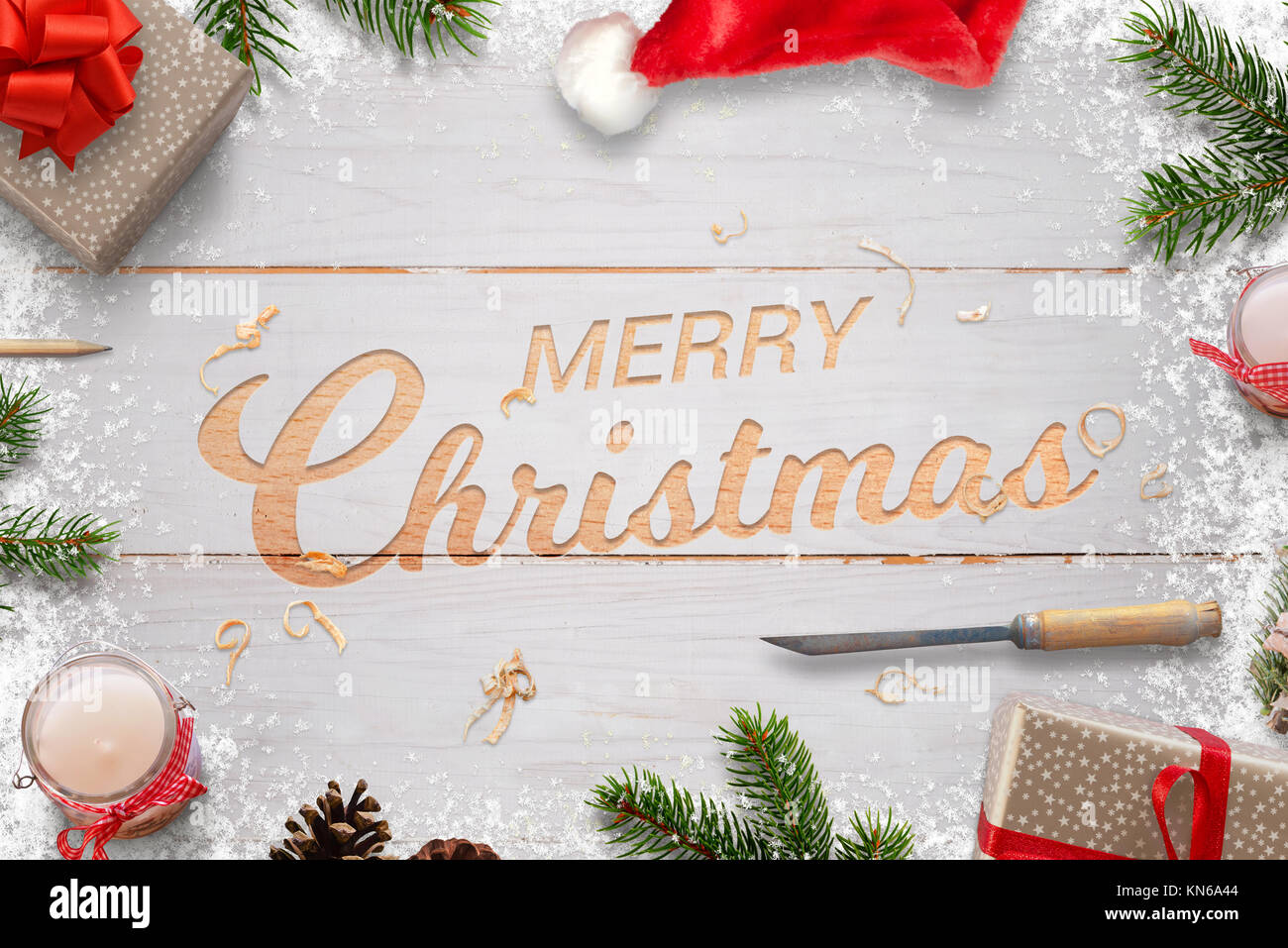 Christmas carving in white wooden board. Merry Christmas greeting text surrounded with decorations. - Stock Image