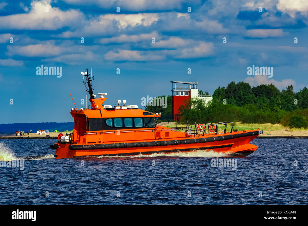 Orange pilot boat moving by the river in Europe. Rescue service - Stock Image