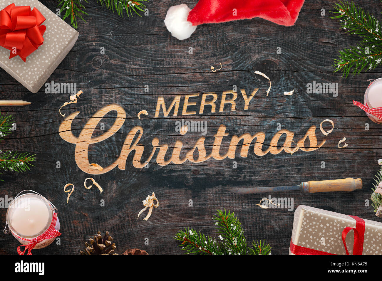 Merry Christmas greeting carved into a wooden surface. Christmas gifts, tree branches, chisel, candles, pinecones - Stock Image