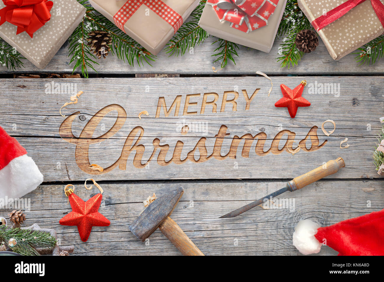 Christmas hand craft on wooden surface with hammer and chisel. Wooden carving greeting text surrounded with gifts - Stock Image