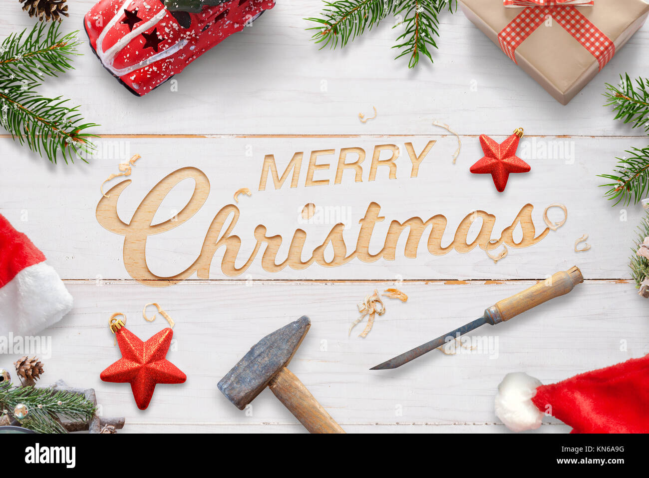Creative Chrtistmas greeting with carved text on white wooden surface with hammer and chisel. Christmas decorations - Stock Image