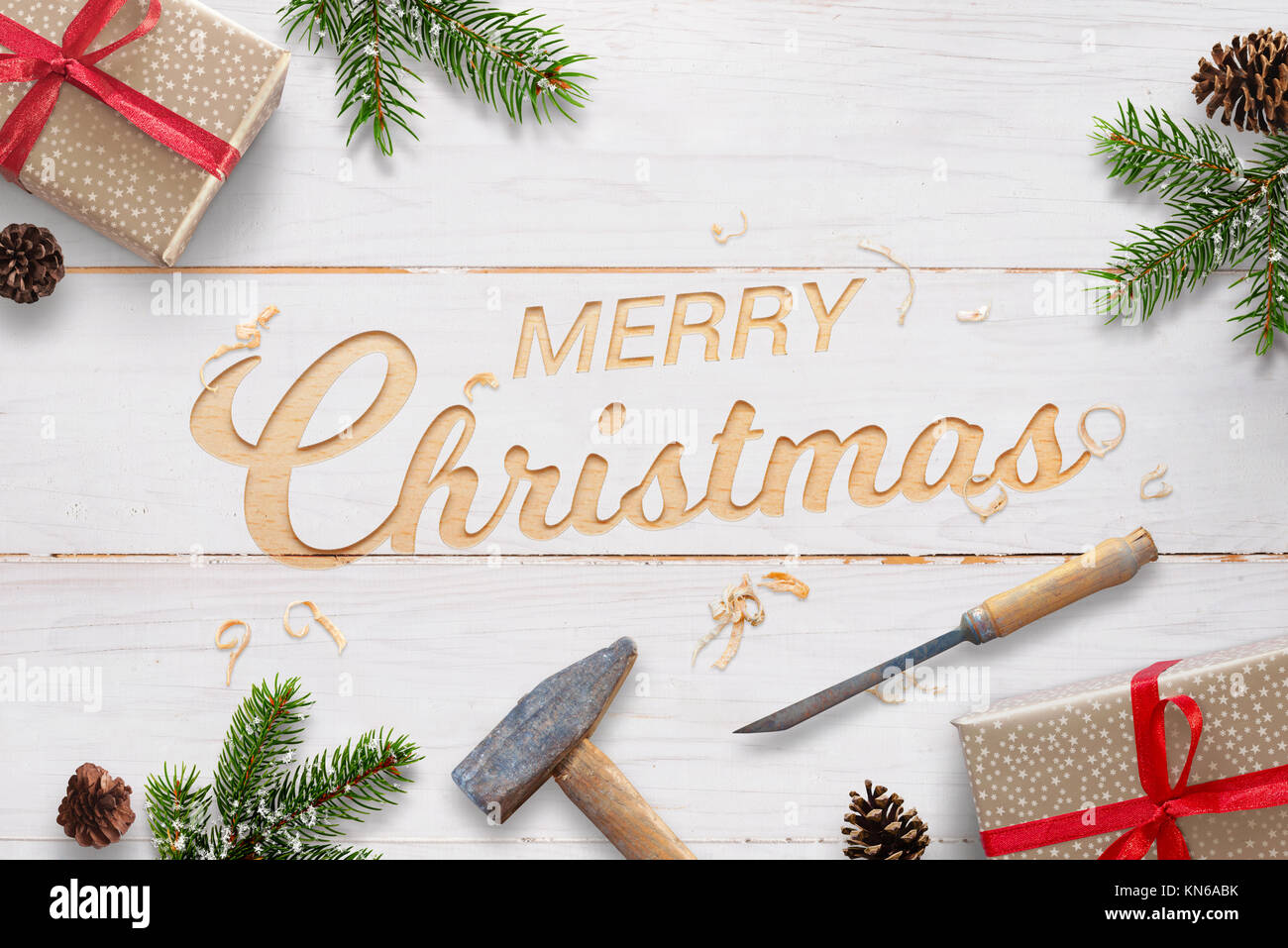 Flat Christmas greeting with carved text into white wooden surface with chisel and hammer. Christmas fir branches, Stock Photo