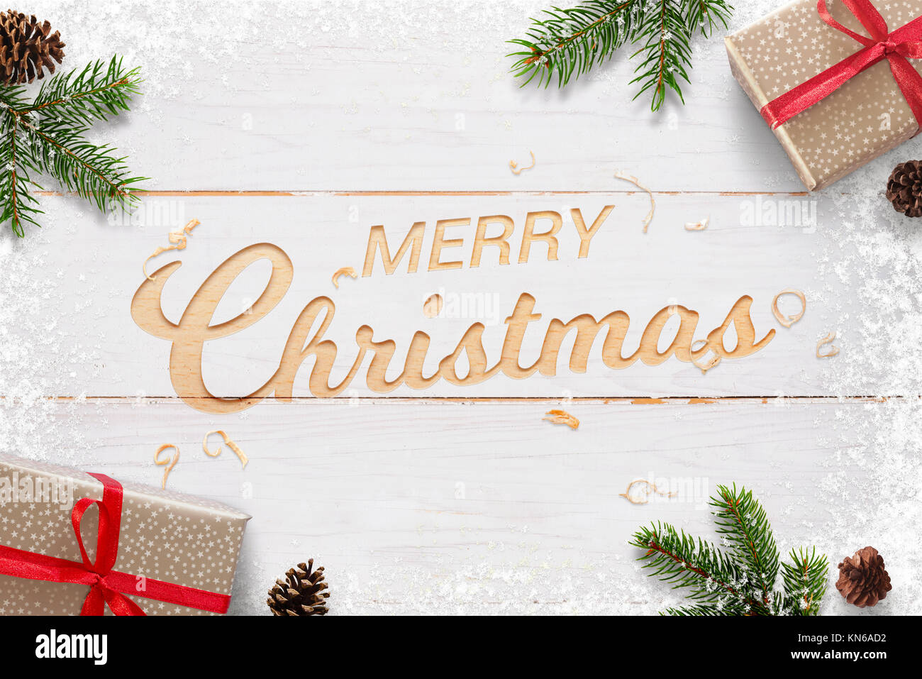 Merry Christmas text hand carved in white woodej surface surrounded with Christmas gifts, fir branches and pinecones. - Stock Image