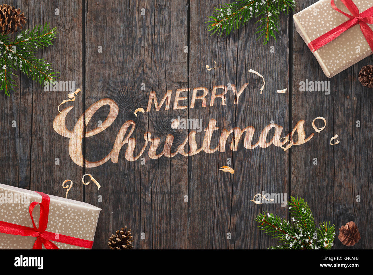Christmas greeting text hand carved on dark wooden surface with Christmas decorations. Gifts, fir branches and pinecones - Stock Image