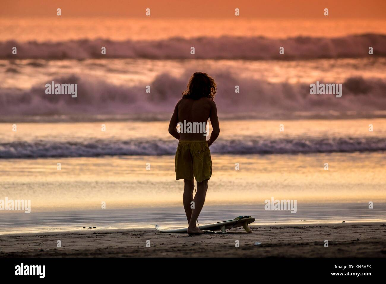 Surfer on the Beach at Sunset Tme, Bali, Indonesia. Stock Photo